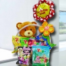 12 inch bear sits in a basket, surrounded with sweets and a balloon